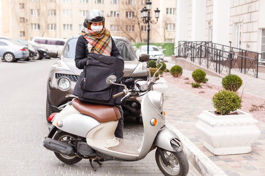 masked woman delivering food on a motorcycle