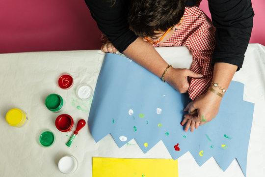 profesora educación especial y alumno con bata están pintando con las manos una corona de cumpleaños y una cartulina amarilla con pinturas acrilicas sobre la mesa. terapia de manualidades plásticas.