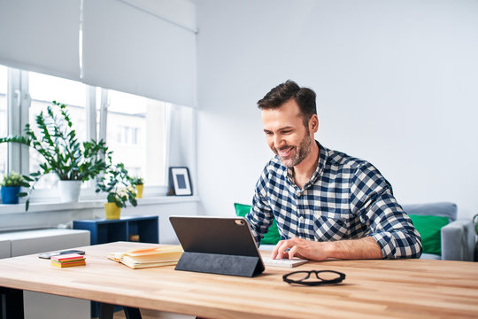 Freelancer working from home sitting at desk with digital tablet