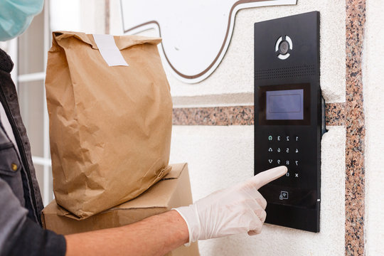 Courier's hands in latex white medical gloves deliver parcels in brown cardboard boxes to the door during the epidemic of coronovirus,COVID-19.Safe delivery of online orders during the epidemic.