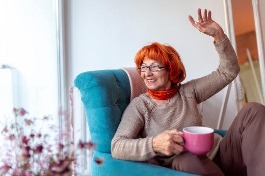 Senior woman waving through the window