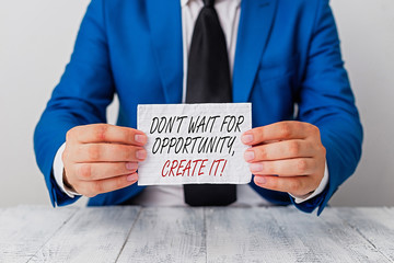 Conceptual hand writing showing Dont Wait For Opportunity Create It. Concept meaning work hard yourself and begin this moment Man holds empty paper with copy space in front of him Space
