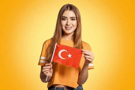 A beautiful young woman holds in her hands the flag of Turkey. Exchange student learning a foreign language. Tourist traveling. Turkish bride. Football fan.