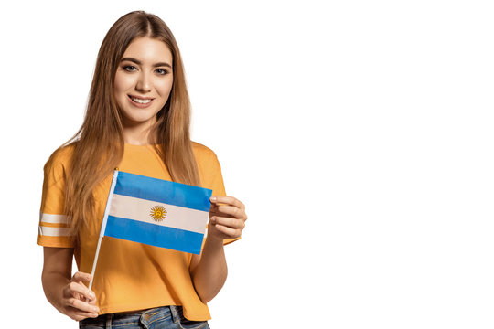 A beautiful young woman holds in her hands the flag of Argentina. Exchange student, learn language. Tourist traveling. White background. Isolate. Football fan.
