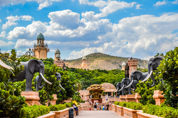 Entrance of The Palace / Lost City /Sun City with stone statues under blue and cloudy sky