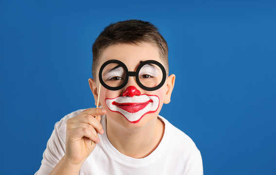 Preteen boy with clown makeup and party glasses on blue background. April fool's day