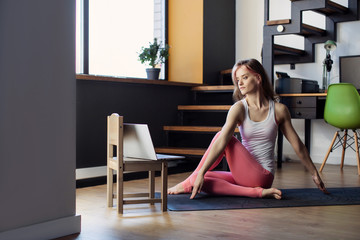young girl goes yoga sports online  at home. stretching in quarantine self-isolation of...