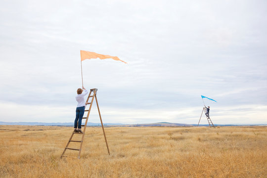 Man and woman couple on ladders waving signal flags. People social distancing relationships separation communication concept.
