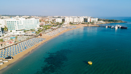 Aerial bird's eye view of Sunrise beach Fig tree, Protaras, Paralimni, Famagusta, Cyprus.The famous tourist attraction family bay with golden sand, boats, sunbeds, restaurants, water sports from above