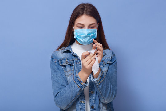 Indoor shot of woman wearing stylish demin jacket and medical blue mask cleaning her hands with wipe isolated over blue background in studio. Coronavirus, covid 19, quarantine, health care concept.