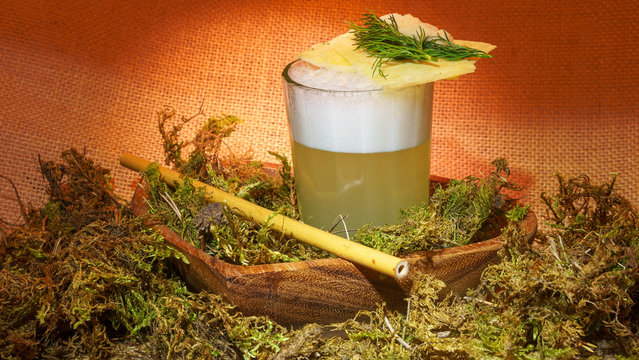Signature moonshine cocktail with bamboo straw and moss on sackcloth background. Alcohol concept.