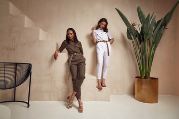 Two beautiful woman fashion model brunette hair friends wear overalls suit casual style sandals high heels accessory clothes safari Sahara journey summer hot collection plant flowerpot wall stairs.