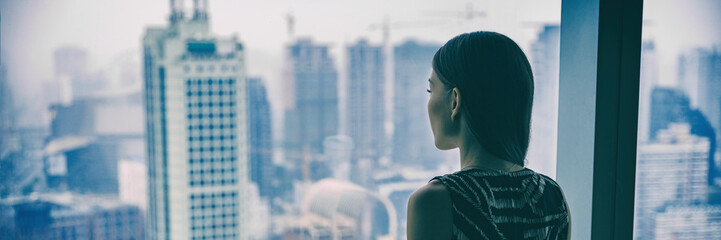 Fototapeten Shanghai COVID-19 Quarantine mental health. Woman self isolated at home pensive looking out of high rise building window at city skyline thinking of relationship, employment, coronavirus. Panoramic banner.