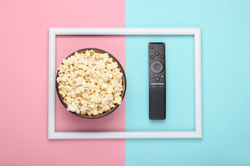 Bowl of popcorn and tv remote on pink blue pastel background with white frame. Leisure and...
