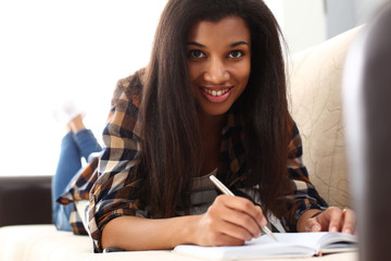 Smiling black woman write story in notebook preparing for college
