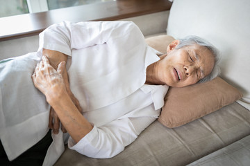 Sick asian senior woman with stomach ache,old people having aching belly,hands touching stomach painful,gastritis,gastric ulcer,severe pain,chronic abdominal problems,colorectal cancer,elderly disease