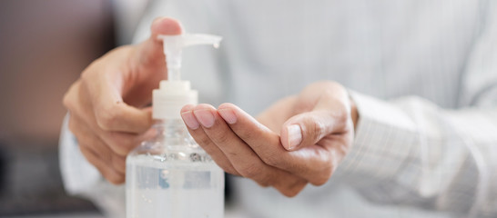 Man hands using wash hand alcohol gel or sanitizer bottle dispenser, against Novel coronavirus or Corona Virus Disease (Covid-19) . Antiseptic, Hygiene and Health concept