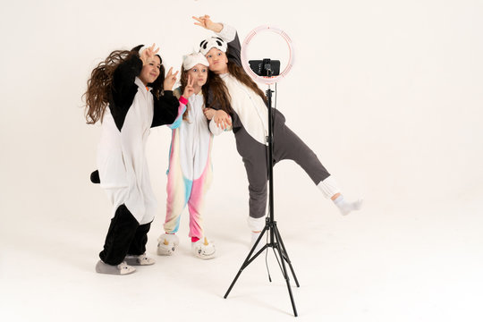 Cute teenage girls in kigurumi and sleep masks smiling and shoots a video. Selfies. The phone is mounted on a tripod and the ring lamp shines