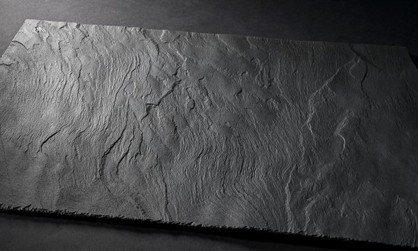 black matte slate natural stone plate with textured surface on gray background