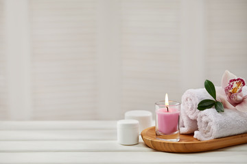 Printed kitchen splashbacks Spa Spa products with aromatic candles, orchid flower and towel on white wooden table. Beauty spa treatment and relax concept. copy space