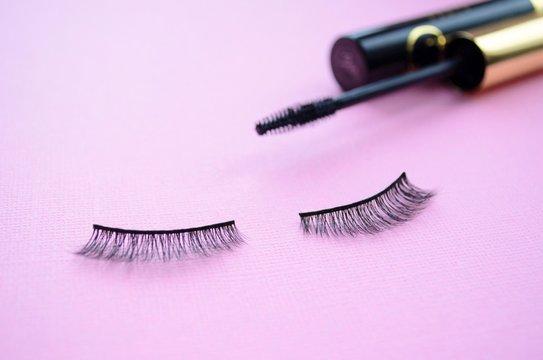 false eye lashes and black mascara on a purple background. Mascara or false lashes?