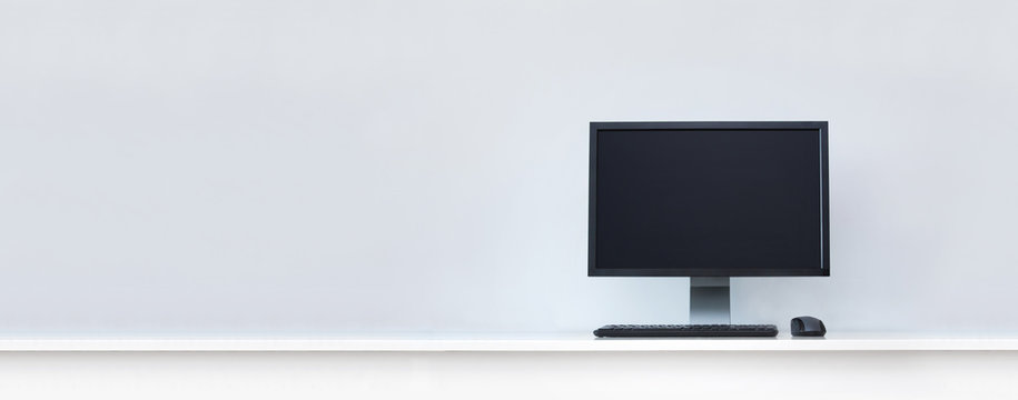 Clean white desk with computer and copy space.
