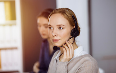 Businesswoman talking by headset in sunny office. Call center and diverse people group in business Fototapete