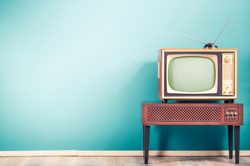 Photo sur Plexiglas Retro Retro old outdated classic television receiver with TV antenna from circa 60s of XX century on wooden stand with amplifier front gradient mint blue wall background. Vintage style filtered photo