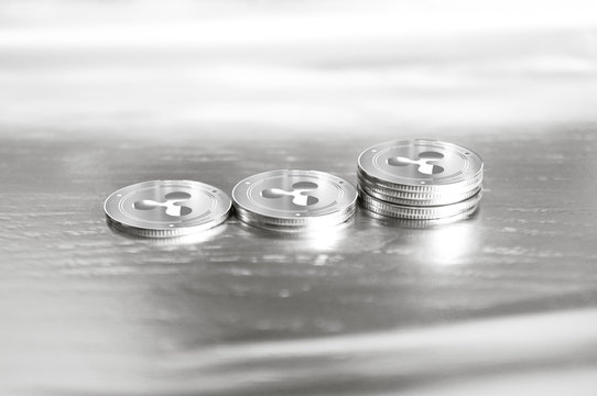 Ripple (XRP) digital crypto currency. Stack of silver coins. Cyber money.