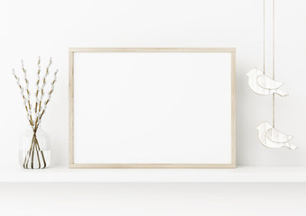 Horizontal poster frame mockup. Spring interior decoration with willow branches and hanging birds on empty white wall background. A4, A3 size format. 3D rendering, illustration.