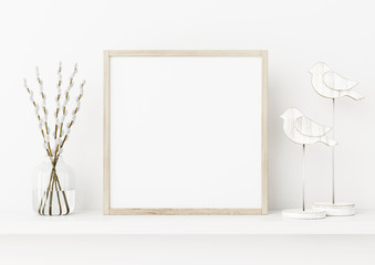 Square poster frame mockup. Spring interior decoration with willow branches and wooden birds on empty white wall background. 3D rendering, illustration.