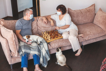 Elderly couple in medical masks during the pandemic coronavirus play chess