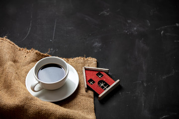 White cup of coffee and little house on dark background