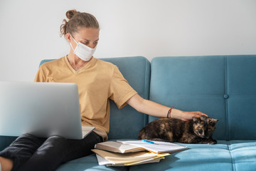Young girl employee in mask with laptop computer in self isolation working from home, coronavirus...