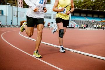 Wall Mural - two man athletes run on track of stadium marathon race