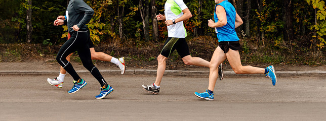 Fotomurales - group male runners athletes run a marathon in park on road