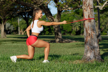 Athletic woman workout squats with resistance band outdoors. Fitness girl doing exercise for back and legs at the park Fotomurales