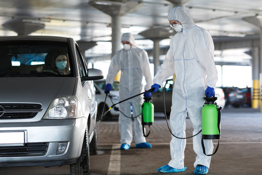 Men in a protective suit and mask disinfecting car with spray
