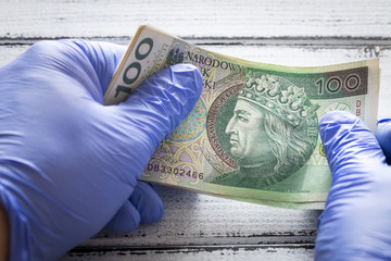 Polish money, one hundred zlotys banknotes kept in rubber gloves.  The concept of economy and financial threats during the Coronavirus pandemic Wall mural