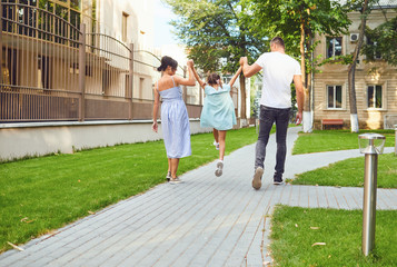 Obraz Happy family walking together in the street of the city - fototapety do salonu