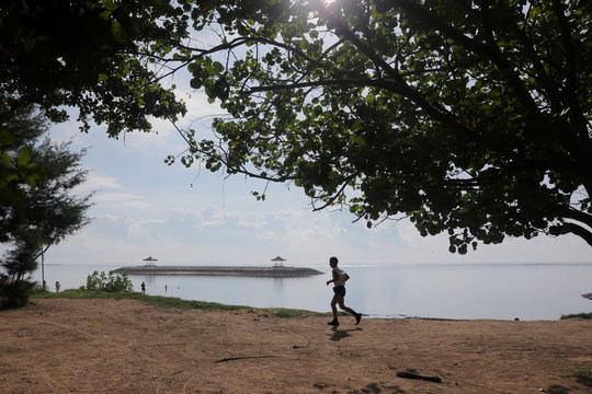 A man runs at Sanur beach amid the spread of coronavirus disease (COVID-19) outbreak in Bali