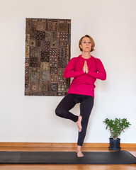 Middle aged woman practicing yoga, Tree pose.