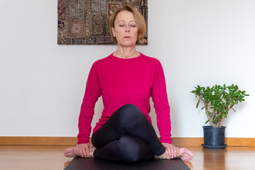 Middle aged woman practicing yoga at home, cow face pose.