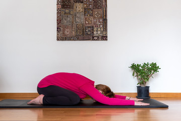 Middle aged woman sitting in Child exercise, Balasana pose. Yoga at home concept.