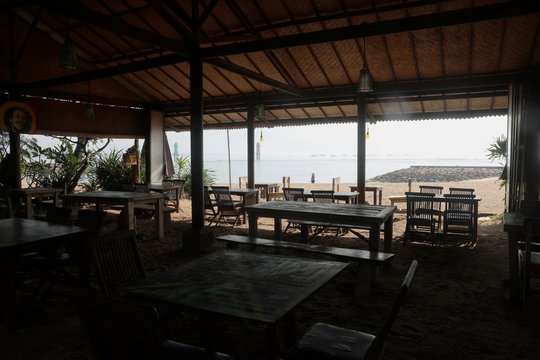 An empty restaurant is pictured with a tourist walking in the background, amid the spread of coronavirus disease (COVID-19) outbreak, at Sanur beach in Bali