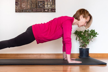 Middle aged woman practicing yoga at home. Phalankasana pose .