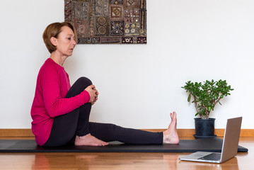 Middle aged woman watching yoga exercises online video tutorial  on her laptop. Yoga at home concept.