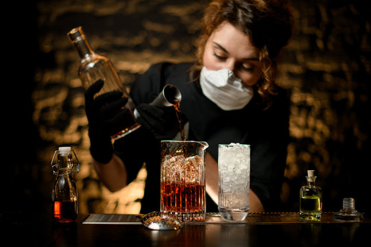 Lady bartender pours alcoholic drink into large glass with ice.
