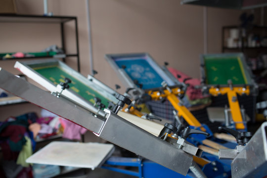 Silk screen printing. Serigraphy. Color paints and fabric. Carousel machine.