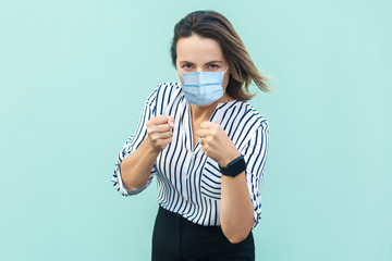 Portrait of serious middle aged woman with surgical medical mask standing with boxing fists and...